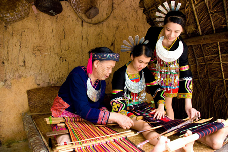 Old lady teaching her young how to weaving in Li and Miao Minority Village.
