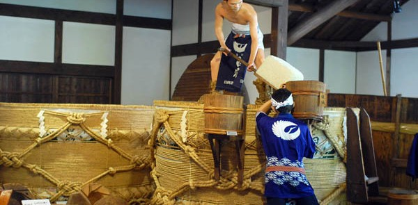 Two men performing sake-making steps in Hakutsuru Sake Brewery